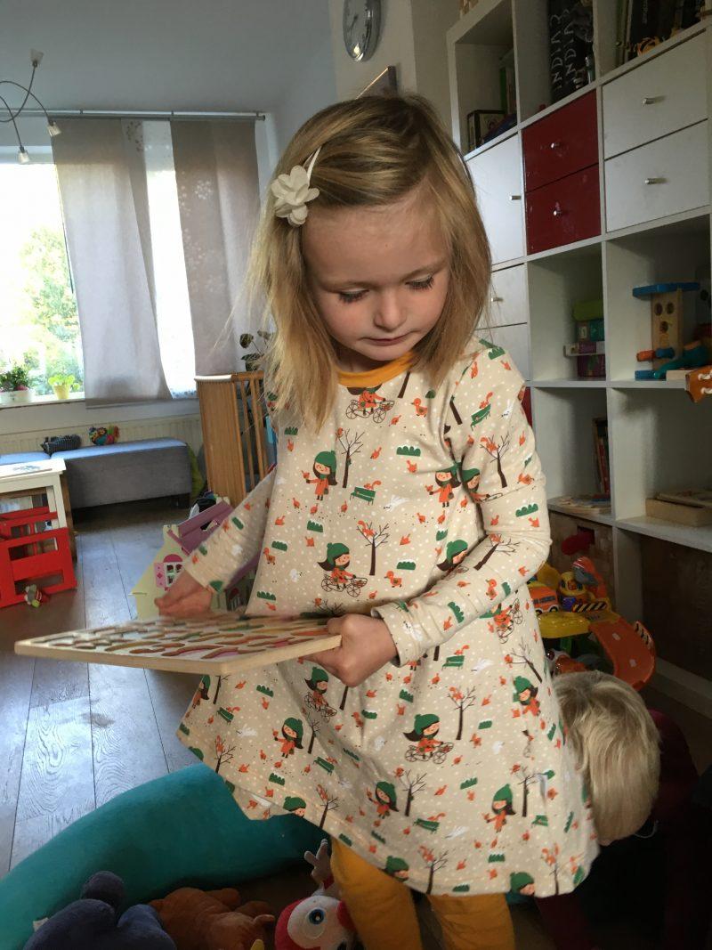 Isa, een meisje van 6 in haar t-shirtjurk in oranje en groentinten.