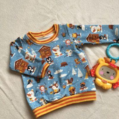 T-shirt met dieren die warme chocomel drinken in oranje en bruin op een lichtblauwe achtergrond